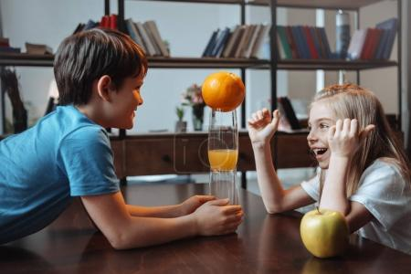 Boy and girl playing with glasses and fruits