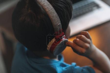 kid boy listening music in headphones