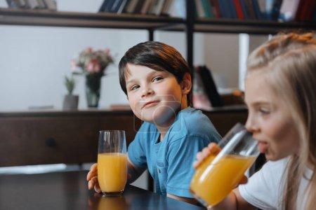 boy and girl drinking orange juice
