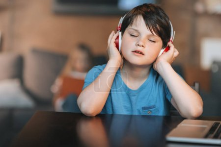 Photo for Kid boy listening music in headphones while sitting at home - Royalty Free Image