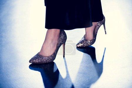 Foto de Vista recortada de la elegante mujer glamour caminando en tacones altos brillo y vestido largo con retroiluminación - Imagen libre de derechos