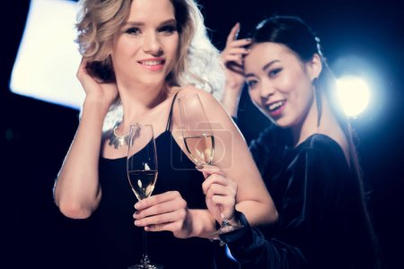 Photo for Smiling seductive multiethnic girls toasting with champagne glasses and having fun at party - Royalty Free Image