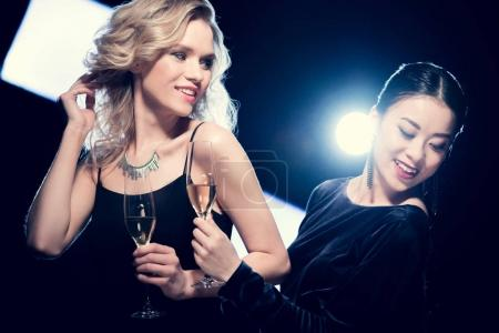 Photo for Attractive smiling glamour multicultural girls drinking champagne at party - Royalty Free Image