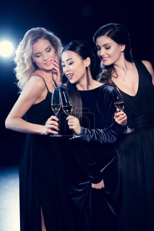 Photo for Beautiful young women in stylish dresses partying and drinking champagne together - Royalty Free Image