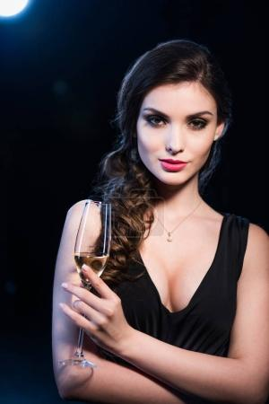 Photo for Portrait of seductive young woman in evening gown holding glass of champagne looking at camera - Royalty Free Image