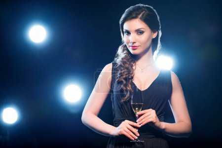 Photo for Seductive brunette woman holding glass of champagne and looking at camera - Royalty Free Image