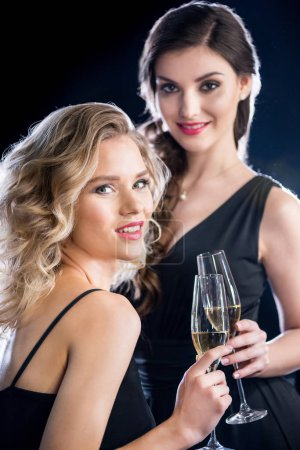 Photo for Gorgeous smiling young women in evening gowns holding glasses of champagne and smiling at camera - Royalty Free Image