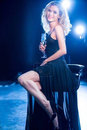 Photo pour Souriante jeune femme en robe de soirée, tenant le verre de vin tout en étant assis sur le tabouret - image libre de droit