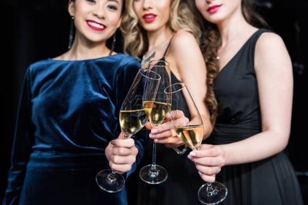 Photo pour Vue partielle des femmes souriantes dans des robes élégantes cliquetis verres avec champagne - image libre de droit