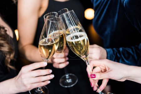 Photo for Partial view of women holding glasses with champagne in hands - Royalty Free Image