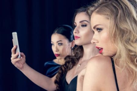 Photo pour Jeunes femmes à la mode prenant selfie sur smartphone ensemble - image libre de droit