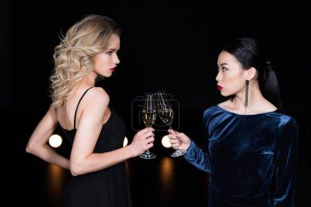 Photo pour Jeunes filles glamour en robes de soirée cliquetis avec des verres de champagne à la fête - image libre de droit