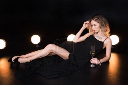 Photo pour Jeune femme blonde glamour tenant à Champagne et à la recherche de suite - image libre de droit