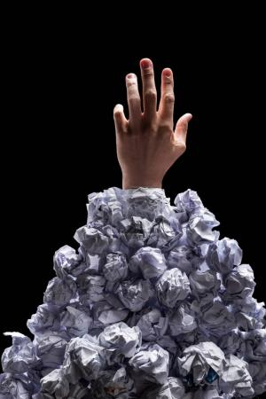 Photo for Cropped shot of hand reaching out from heap of crumpled papers isolated on black - Royalty Free Image