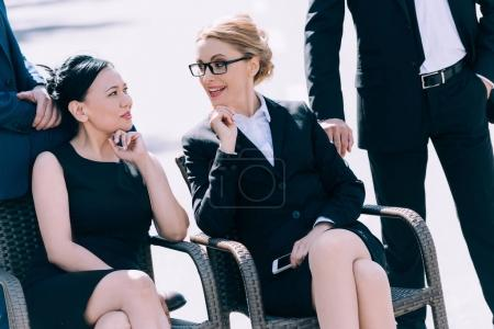 mature businesswomen sitting on chairs