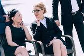 mature businesswomen sitting on chairs