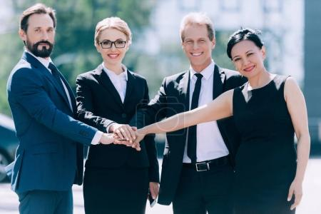multiethnic businesspeople stacking hands