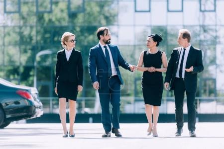 Photo for Multiethnic group of professional middle aged businesspeople walking together and talking on street - Royalty Free Image