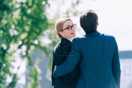business colleagues embracing on street