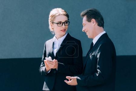 Photo pour Souriant homme d'affaires mature regardant femme d'affaires blonde en utilisant un smartphone - image libre de droit