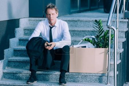 Photo pour Tiré cher homme d'affaires mature tenant smartphone tout en étant assis sur les escaliers avec boîte en carton - image libre de droit