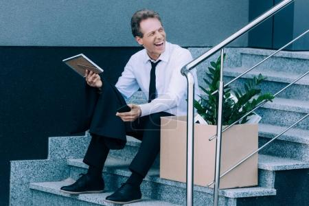 Photo for Fired laughing mature businessman sitting on stairs with cardboard box and looking away - Royalty Free Image