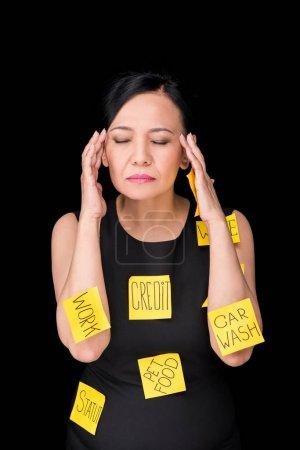 Photo pour Stressé mature asiatique femme avec collant notes sur vêtements et corps debout avec les yeux fermés isolé sur noir - image libre de droit