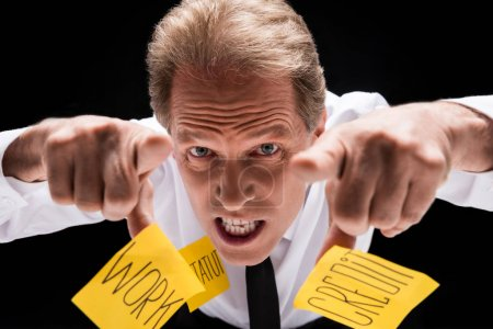 Photo for Angry middle aged businessman with sticky notes on clothes pointing at camera isolated on black - Royalty Free Image