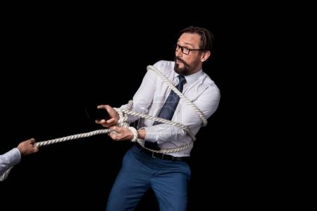 person pulling tied businessman