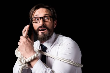 tied businessman holding smartphone