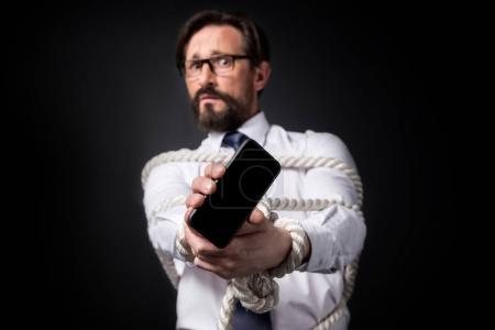 Photo pour Homme d'affaires mature effrayé avec les mains liées tenant smartphone avec écran vide isolé sur noir - image libre de droit