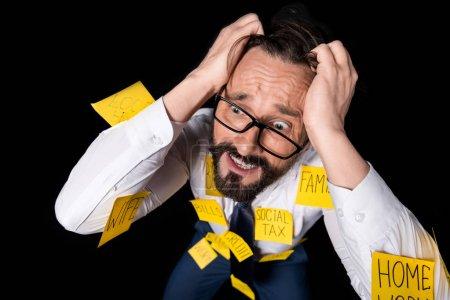 Photo pour Frustré homme d'affaires d'âge moyen avec des notes collantes sur les vêtements agenouillés et les cheveux déchirants isolés sur noir - image libre de droit