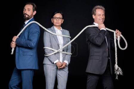 businessmen tying businesswoman with rope