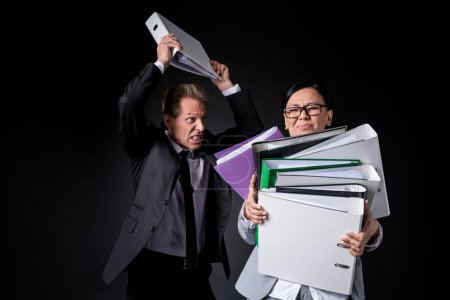 Photo for Overworked mature businesswoman holding folders while angry male colleague able to hit isolated on black - Royalty Free Image