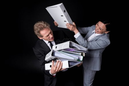 Photo for Excited asian businesswoman with folder fighting with scared businessman holding folders isolated on black - Royalty Free Image