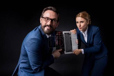 Photo pour Excités collègues matures se battant pour ordinateur portable avec écran vide isolé sur noir - image libre de droit