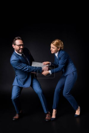 business colleagues fighting for laptop