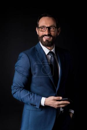 Photo for Handsome bearded mature businessman holding smartphone and looking away isolated on black - Royalty Free Image