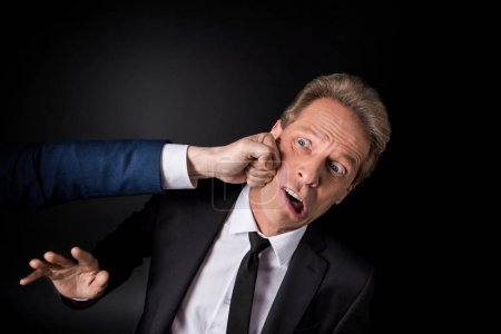 Photo for Cropped shot of hand punching middle aged businessman isolated on black - Royalty Free Image