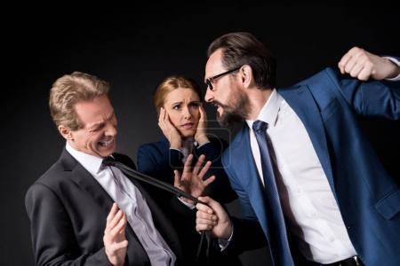 Photo pour Hommes d'affaires matures se battant tandis que femme d'affaires effrayée debout derrière isolé sur noir - image libre de droit