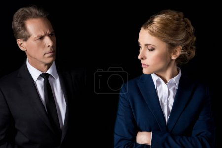 Photo for Serious middle aged businesswoman standing with crossed arms and looking at colleague isolated on black - Royalty Free Image