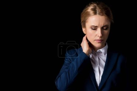 Photo for Tired middle aged business woman with headache holding hand on neck isolated on black - Royalty Free Image