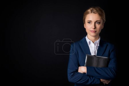 Photo for Pensive middle aged businesswoman holding digital tablet and looking away isolated on black - Royalty Free Image