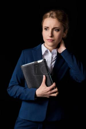 Photo for Tired middle aged businesswoman holding digital tablet and looking away isolated on black - Royalty Free Image