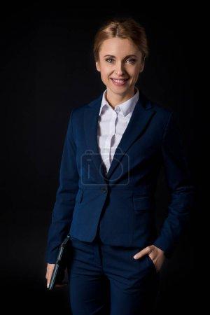 Photo pour Confiant blonde femme d'affaires tenant tablette numérique et souriant à la caméra isolé sur noir - image libre de droit
