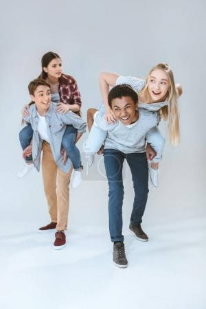multicultural teenagers piggybacking together
