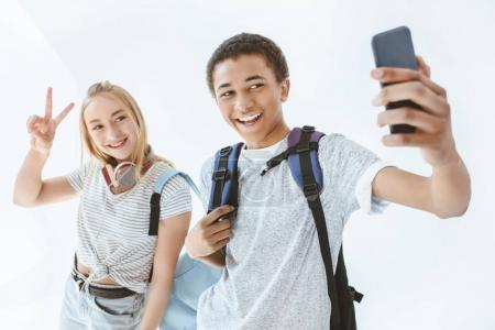 Photo for Portrait of multicultural teenagers taking selfie together on smartphone isolated on white - Royalty Free Image