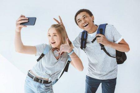 Foto de Adolescentes felices multiculturales teniendo selfie juntos en smartphone aislado en blanco - Imagen libre de derechos