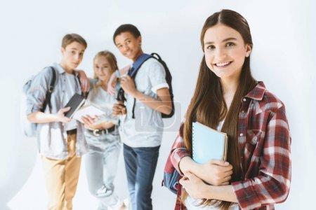 Photo pour Adolescente souriante avec ordinateur portable dans les mains regardant la caméra avec des étudiants multiculturels derrière isolé sur blanc - image libre de droit