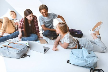 multicultural teenagers with laptop